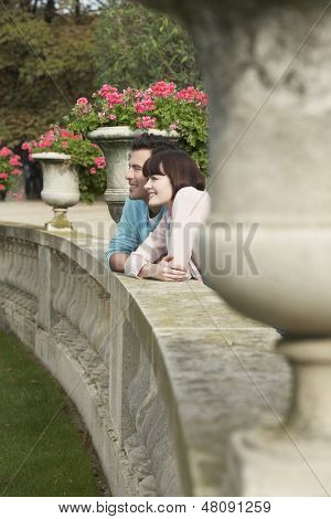 Side view of a smiling couple looking over wall by potted plants