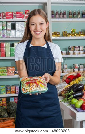 Portrait of beautiful saleswoman holding vegetable packet in grocery store