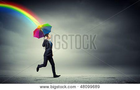 Businessman in black suit with umbrella atop of building