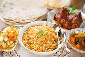 Indian meal biryani rice, chicken curry, masala milk tea, acar vegetable, roti chapatti and papadom. poster