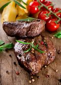 Delicious beef steaks on wooden table poster