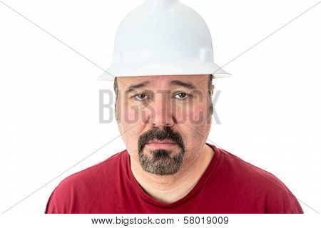 Morose glum looking man with a goatee beard wearing a hardhat looking at the camera with lacklustre eyes and a depressed expression isolated on white poster