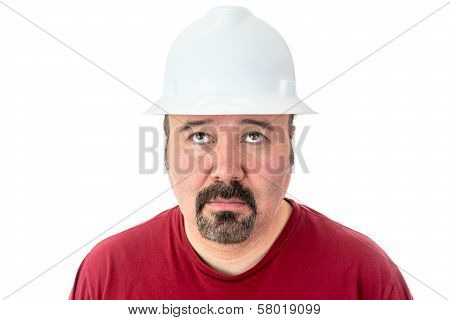 Glum looking workman wearing a hardhat looking for inspiration raising his eyes to the heavens in supplication isolated on white poster