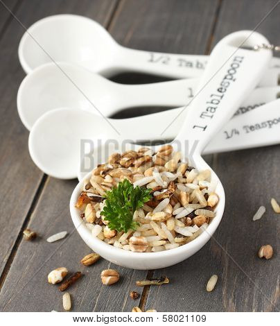 Uncooked Multigrain Rice In Porcelain Measuring Spoons On Wooden Background
