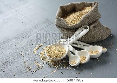 Quinoa Grain In Small Burlap Sack And Porcelain Measuring Spoons