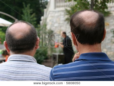 Two Bald Guys Watching an Event