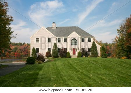 Large Beautiful House On Hill Next To Pond With Fall Colors