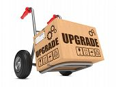 Upgrade Slogan on Cardboard Box on Hand Truck White Background. poster