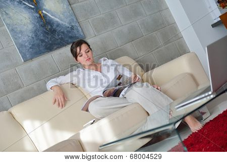 happpy young woman reading magazina at home in comfortabel sofa and bright living room