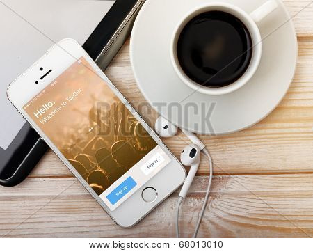 SAINT-PETERSBURG, RUSSIA - March 31, 2014: Photo of  iPhone 5 with home screen of popular social media website Twitter. iPhone 5S is a smartphone developed by Apple Inc.
