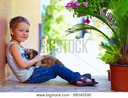 Smiling Boy With Sleeping Puppy In Hands