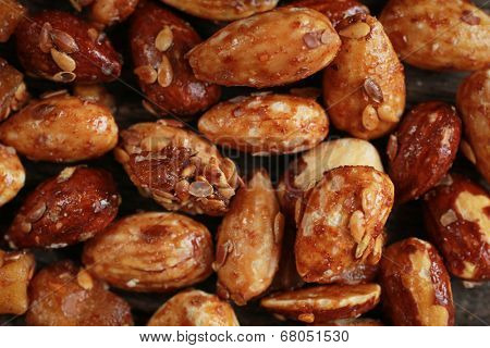 Close up of honey roasted almonds with sesame on a wooden table