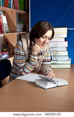 A Student Reading A Book In A Classroom