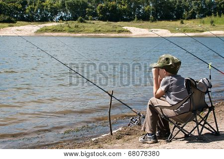 Boy With Fishing Rod Sitting On The Shore Of The Pond.