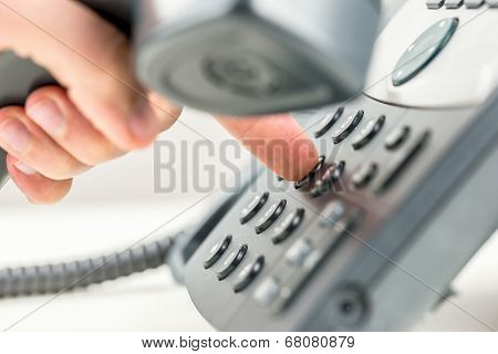 Man Dialling Out On A Telephone