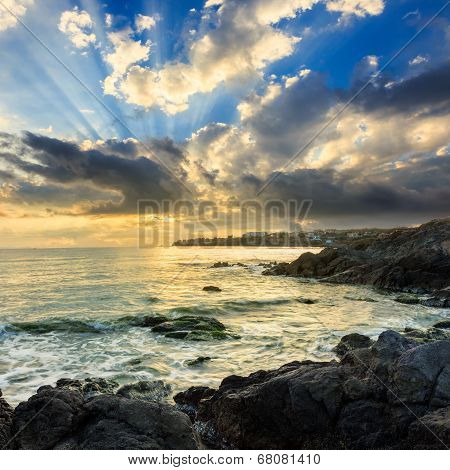Sea Wave Breaks About Boulders At Sunrise