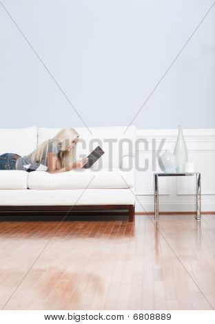 Young Woman Lying On Sofa Reading Book