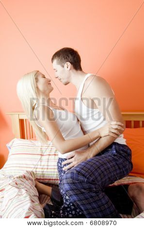 Young Couple Kneeling On Bed Embracing