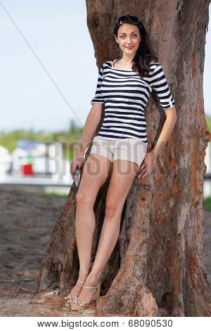 Full body shot of a woman leaning on a tree