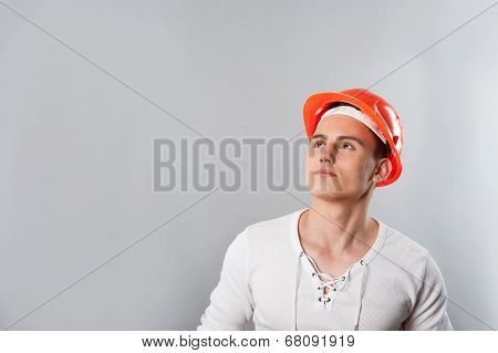 Portrait of a young serious handsome worker in helmet looking up