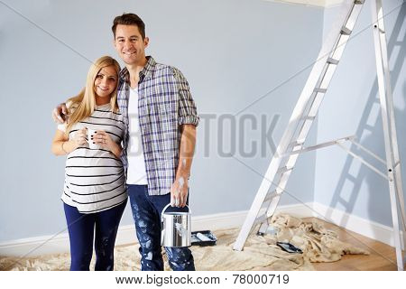 Portrait Of Couple Decorating Nursery For New Baby poster
