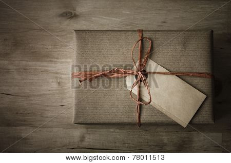 Overhead shot of a gift box with a grungy parcel tag for a label wrapped in brown paper with a raffia ribbon tied to a bow on wooden planked table. Vintage appearance with dark tones and vignette. poster