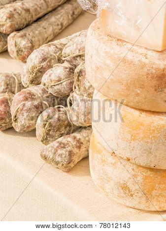 Stacked Rounded Cheese And Group Of Salami On Tablecloth
