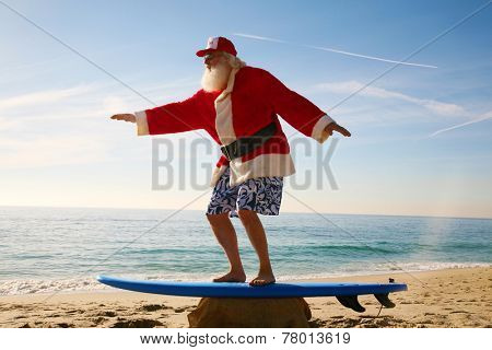 Santa Claus practices his Surfing Skills on his Surf Board on the beach, before he goes into the ocean. Santa Loves the Beach when on vacation from delivering gifts to good boys and girls at christmas poster