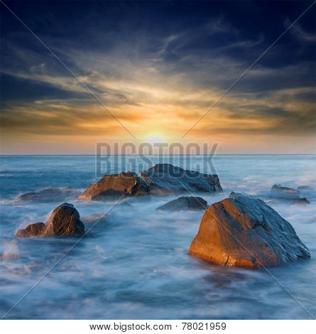 Sunset on sea shore with stones in water