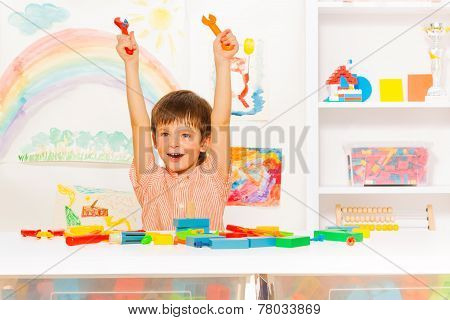 Cute happy boy with wrenches in the kindergaten