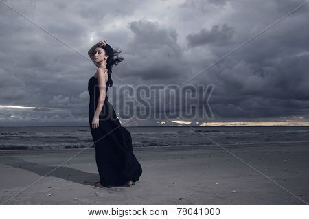 Beautiful Brunete Model In Long Black Dress Standing On The Beach. Cloudy Weather. Sunset