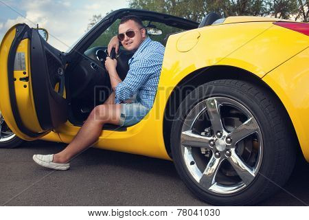 Lucky Young Man Sitting In His New Convertible Car. Low Angle View