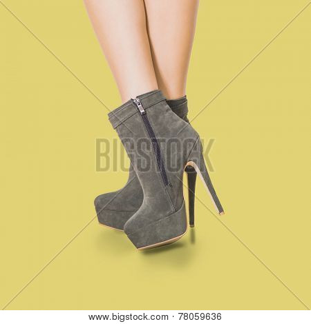 woman legs in velour high heel platform ankle boots on warm yellow background