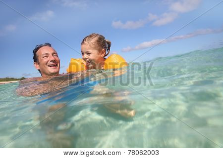 Father and 4-year-old girl bathing in the sea