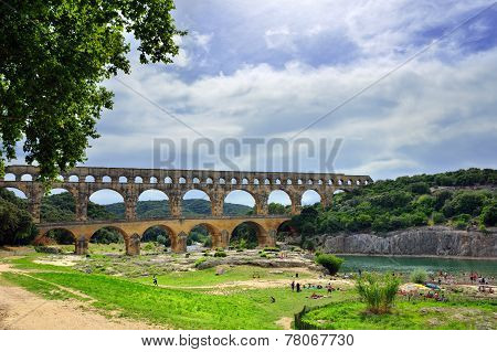 Tourists have a rest on the shore of Gardon river under an old Roman aqueduct Pont du Gard. The Gorge du Gardon is a popular recreation area for kayaking canoeing and hiking poster