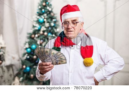 Senior man holding money on Christmas background