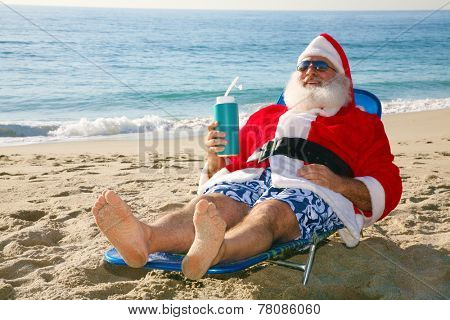 Santa Claus relaxes lying on the beach on some tropical island in the sun. Santa Claus enjoys a well earned vacation after delivering Christmas presents to good boys and girls. Santa loves the beach