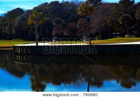 Golf course next to pond.