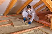Man laying thermal insulation layer under the roof - using mineral wool panels poster