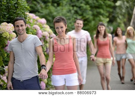 Group of people with couples walking outdoors on a beautiful spring or summer day