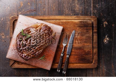 Grilled Black Angus Steak Ribeye On Himalayan Pink Salt Block On Dark Wooden Background