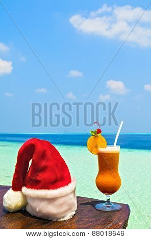 Bocal Of Drink Is On A Beach Table With Santa Hat
