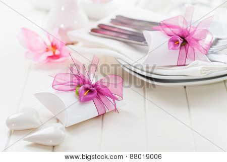 Decorated table in white with small present for the guests