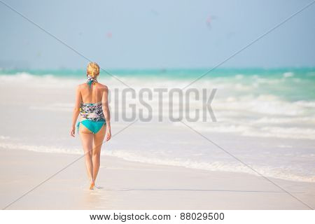 Happy woman having fun, enjoying summer, walking joyfully on tropical beach. Beautiful caucasian model  wearing colorful scarf and turquoise bikini on vacations on Paje beach, Zanzibar, Tanzania