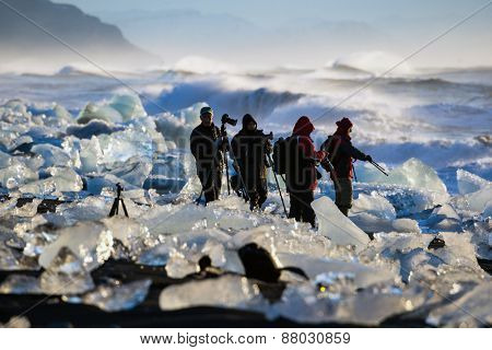 ICELAND - MARCH 26, 2015: Photographers views the sunrise amidst the blocks of ice from the glaciers that break up and washed ashore by the strong waves of the North Atlantic sea in Iceland.