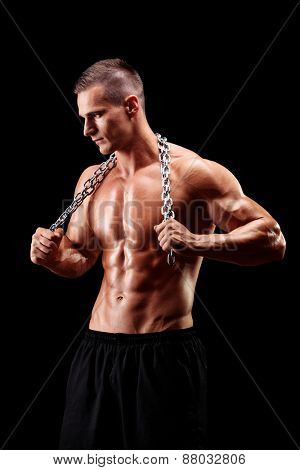 Vertical shot of a shirtless young man holding a chain around his neck on black background