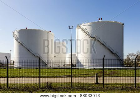 white tanks in tank farm with iron staircase under blue sky poster
