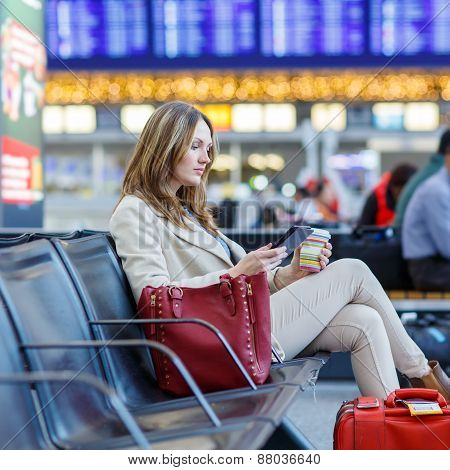 Young woman at international airport reading her ebook computer and drinking coffee to go while waiting for her flight. Female passenger at terminal indoors. poster