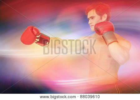 Muscly man wearing red boxing gloves and punching against purple sky