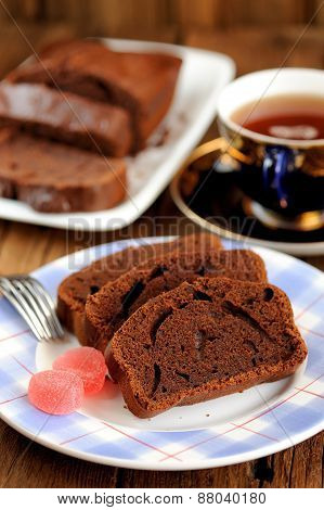 Homemade Chocolate Cake Cut With Pink Candies And Tea In Blue Cup